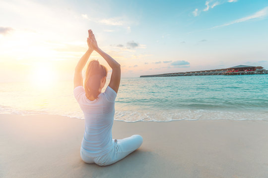 Asian woman wearing white sportswear practicing yoga Lotus pose to meditation on the beach in Maldives at sunset,Feeling so comfortable and relax in holiday,Healthy Concept