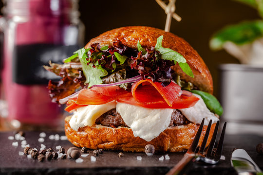Concept of Italian home cooking. Burger with beef and pork meat cutlet, mozzarella cheese, salami sausage, parma, arugula and lettuce mix. Beautiful serving in restaurant.