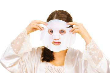 Woman applying sheet mask on face