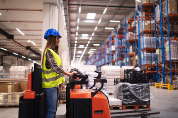 Woman warehouse worker operating forklift machine in large distribution warehouse center. Manual worker relocating goods in factory storage area.