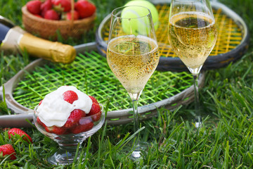 Enjoing in Wimbledon tennis championship with champagne and strawberries with cream. Wimbledon symbols on green grass.