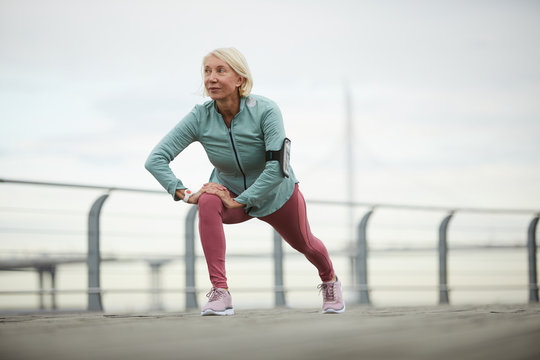 Mature sportswoman doing exercise for stretching legs while working out on bridge in urban environment on summer day