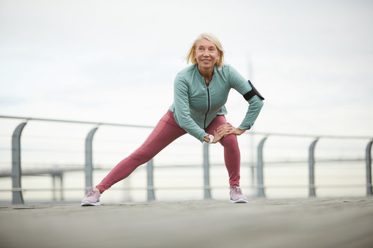 Happy mature sportswoman in activewear enjoying workout in urban environment while doing stretching exercise
