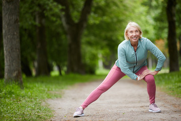 Mature cheerful blonde female in activewear stretching legs while doing physical exercises on road in city park among green trees