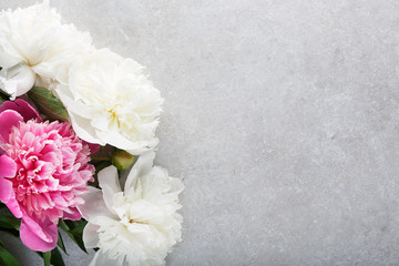 Beautiful pink white peony flowers and tag on gray stone background.
