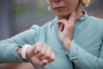 Mature sportswoman checking her pulse while keeping two fingers under neck and looking at wristwatch after workout