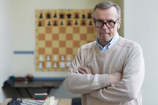 Aged male principal of chess club posing for pictures for advertising chess classes for schoolchildren
