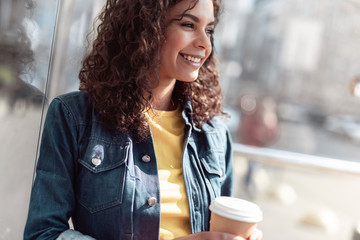 Cheerful young female is having cup of coffee outdoor