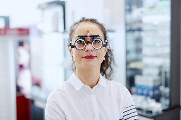 Woman with curly hair and ponytail standing at optician shop with phoropter on. Woman looking at camera.