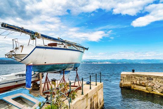 Hafenszene Lovran, Kroatien mit Rijeka im Hintergrund