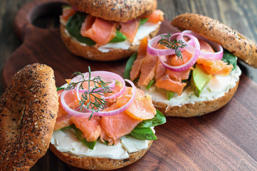 Lox - Everything bagel with smoked salmon, spinach, red onions, avocado and cream cheese over a rustic wood table background. Image shot from top view or flat lay position.