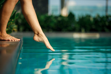 Closeup young female leg touch blue water in swimming pool