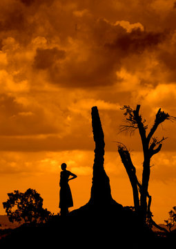Silhouette of a woman standing on a termite mount at sunset, Borana tribe area, Omo valley, Ethiopia.