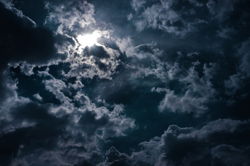 Wall Mural - Moonlight shines behind a cloudy at night. serenity nature background.