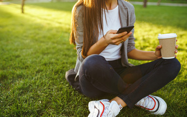 The girl holds the phone and coffee in hand. Image of beautiful stylish woman sitting on green grass with a phone in hand and coffee.  Sunset.  Summertime.