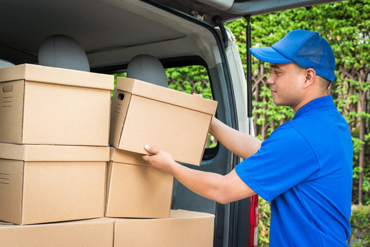 Blue delivery man pick up the parcel cardboard box in the truck