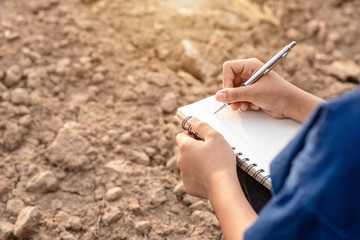 Asian student doing research or checking dry soil in empty land for planting