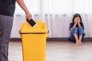 Mother punishing her daughter with throwing smartphone into yellow trash