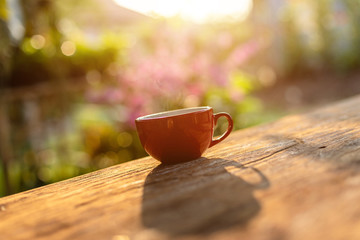 Red coffee cup on wooden table morning nature light in garden concept