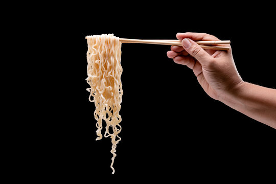 Hand holding bamboo chopsticks and fork over instant noodles