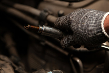A serviceman repairs a car while replacing the spark plugs while holding one of them in hand with a glove while unscrewing them from the engine with traces of soot and black deposits from burned oil