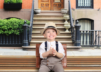 Cute little boy in a hat and trousers with suspenders