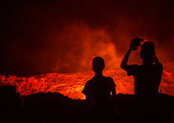 Tourists taking pictures in front of the living lava lake in the crater of erta ale volcano, Afar region, Erta ale, Ethiopia