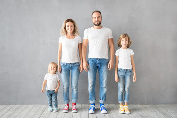Happy family standing against grey background