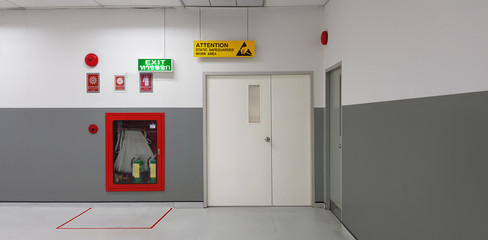 Fire exit way door and fire exit sign lightbox and fire hose in electronic industry ,Green emergency exit sign door direction in case of emergency signage,Fire safety symbol and fire protection. Wall mural