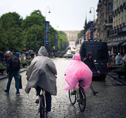 Couple cycling in Oslo's main streat wearing plastic rain ponchos