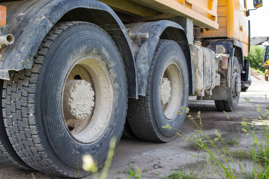 the wheels of the yellow dump truck standing in place