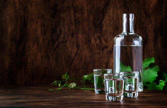 Aguardiente - traditional Spanish strong alcoholic drink, grape moonshine or vodka, in glasses on an old wooden table, place for text
