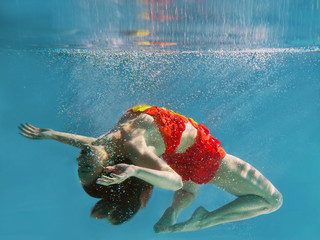 unbelievable, surreal, incredible, amazing underwater portrait of slim, fit woman in bright orange swimming suit