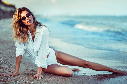 portrait of beautiful sexy caucasian sunbathed woman in sunglasses with long hair in swimsuit lying on summer beach.
