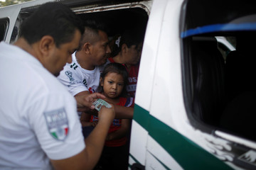 An immigration agent checks IDs at a checkpoint on a road in Tuxtla Chico