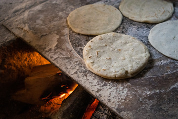 Handmade Tortillas Cooking over Fire in Traditional Guatemalan Kitchen