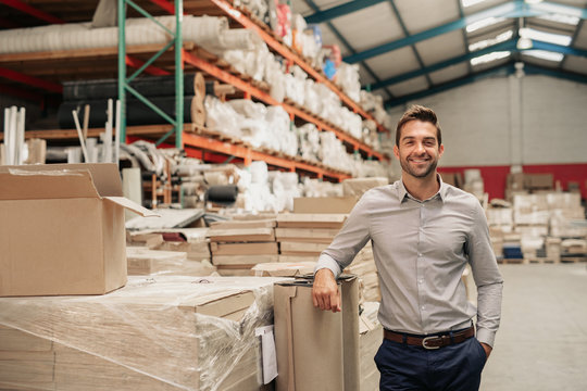Manager smiling while leaning against stock in a large warehouse