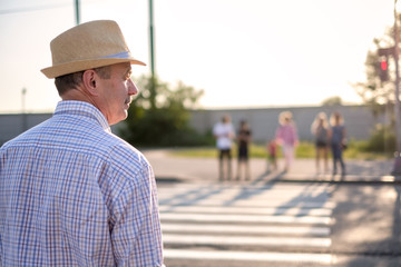 Mature man in summer hat waiting to cross street on sunny day. Fotomurales