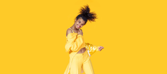 Playful happy young african woman wear stylish yellow clothes look at camera dancing funky black...