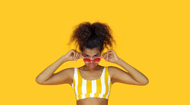 Fashion young african girl black woman wear stylish pink sunglasses glasses looking at camera isolated on summer yellow studio background, horizontal banner for website design, portrait, copy space