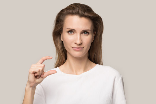 Attractive confident young woman showing small size by fingers