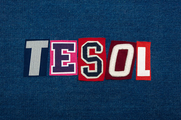 TESOL text word collage, multi colored fabric on blue denim, teach english to speakers of other languages acronym, horizontal aspect