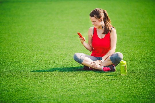 Theme sport health. beautiful young girl sitting resting on green grass. lawn stadium using technodogies. In handphone in ear headphones listens music, summer sportswear watch heart rate monitor