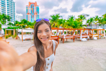 Wall Mural - Travel selfie Asian tourist woman on vacation on South Beach resort hotel in Miami, Florida, USA holiday. Luxury vacations getaway.