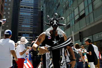 A marcher in black tinted Puerto Rican attire poses with a wooden machete painted in a black and white stripes on 44th Street and 5th Avenue during the annual Puerto Rican Day Parade.