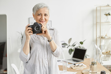 Happy middle aged female photographer with short gray hair holding professional DSLR camera and smiling, posing in stylish office interior with laptop in background. Hobby, creativity and age