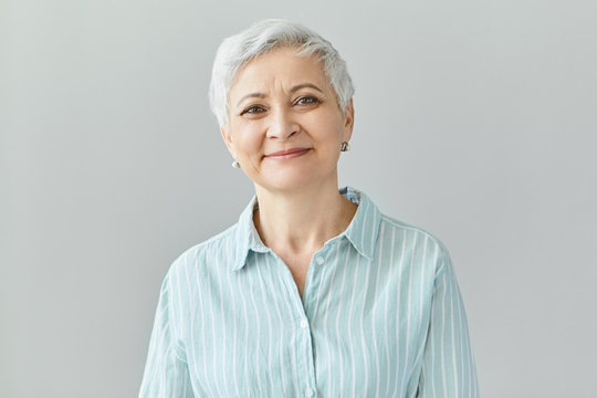Positive human reactions, feelings and emotions. Charming elegant middle aged sixty year old female with short gray hair looking at camera with pleased smile, her eyes full of happiness and joy