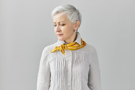 Human facial expressions. Frowning displeased sad female pensioner with pixie gray hair having headache, looking down, posing isolated at blank studio wall with copyspace for your advertising content