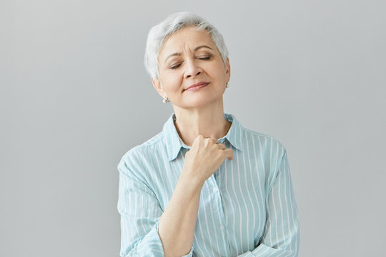 Studio image of beautiful gray haired woman pensioner in blue striped shirt closing eyes and smiling peacefully, enjoying good classical music, having nostalgic facial expression, holding at her chest