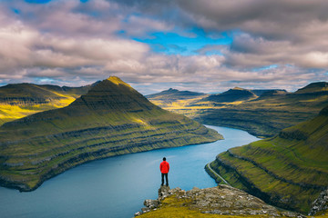 Wall Mural - Hiker enjoys views over fjords from a mountain near Funningur on Faroe Islands